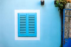 old blue window with wooden shutters in the white frame on the blue wall. - stock photo