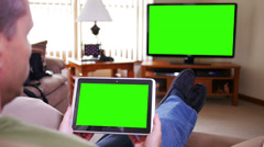 Stock Video Footage of Man with Green Screen iPad Watches TV