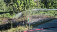 Stock Video Footage of Water Sprayed onto Brush Fire