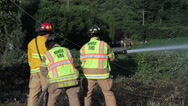 Stock Video Footage of Male & Female Firefighter Team Fights Brush Fire #2