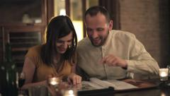 Couple looking at photos in photo album by the table HD - stock footage