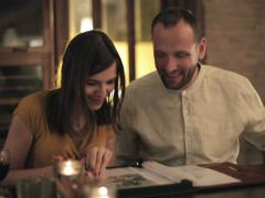 Couple looking at photos in photo album by the table NTSC - stock footage