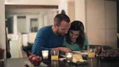 Couple looking at photos in magazine, photo album at home HD - stock footage
