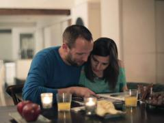 Couple looking at photos in magazine, photo album at home NTSC - stock footage