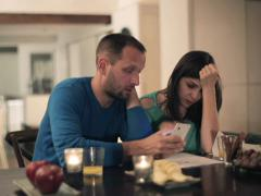 Sad, overwhelmed couple counting bills by the table at hom home table front NTSC Stock Footage