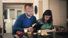 Happy young couple calculating bills by the table at home HD Stock Footage