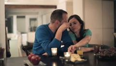 Happy couple talking and eating snacks by the table at home HD Stock Footage