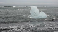 Stock Video Footage of Big peace of blue ice at the black sand beach near Glacier lagoon, Iceland