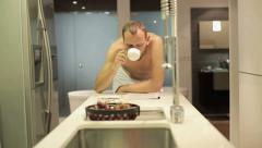 Man in towel after shower reading magazine by table in kitchen HD Stock Footage