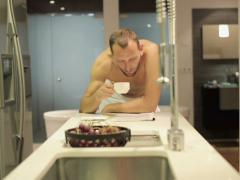 Man in towel after shower reading magazine by table in kitchen NTSC Stock Footage