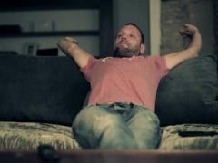 Sleepy young man stretching and yawning on sofa at home NTSC - stock footage