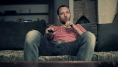 Man watching tv and drinking beer on comfortable sofa HD Stock Footage