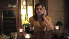 Angry woman talking on cellphone by the table at home HD Stock Footage
