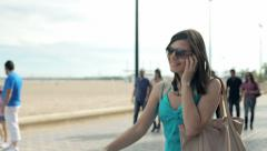 Young woman talking on cellphone on broadwalk by the beach HD Stock Footage