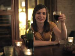 Happy woman raising toast to camera with glass of wine NTSC - stock footage