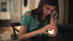 Beautiful sad, pensive woman sitting by the table at home HD Stock Footage