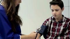 Nurse measuring blood pressure of teenager boy during visit - stock footage