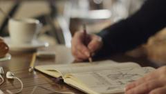 Drawing on sketchbook in coffee shop - stock footage