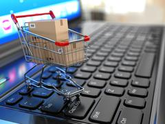 E-commerce. shopping cart with cardboard boxes on laptop. Stock Illustration