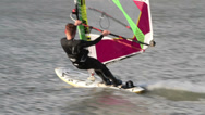 Stock Video Footage of male windsurfer in wet suit speeds past close by