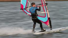 Male windsurfer in wet suit speeds past close by Stock Footage
