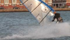 Male windsurfer in wet suit turns to change direction Stock Footage