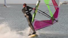 Male windsurfer spins board to change direction Stock Footage