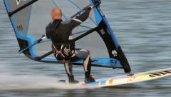 Male windsurfing in wet suit turns to change direction Stock Footage