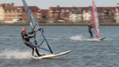 Male windsurfer spins board to change direction and falls Stock Footage