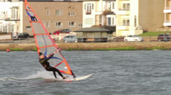 Male windsurfer sails on lake past buildings Stock Footage