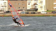 Stock Video Footage of male windsurfer sails on lake past buildings