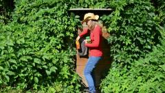 Country woman came into cellar overgrown with green creepers Stock Footage