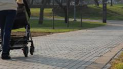 Mother with stroller walks in the park Stock Footage