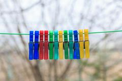 row of colorful clothespins hanging on a green rope in a gerden with blurred - stock photo