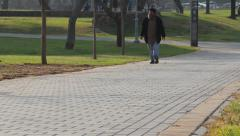 Single man walking in the park Stock Footage