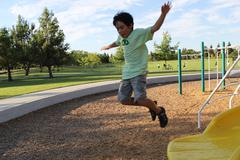 Boy Jumps From Slide Stock Photos
