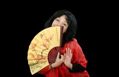black-haired woman plays with japanese fan - stock photo