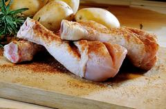 Chicken thighs and potatoes on a chopping board Stock Photos