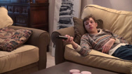 Stock Video Footage of Lazy teenage boy watching TV, laying on a couch, changes channels