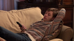 Lazy teenage boy watching TV, lying on a couch, changes channels - stock footage