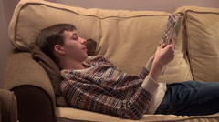 Teenage boy reading an illustrated magazine, young man lying on a couch Stock Footage