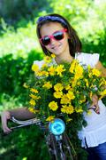 Stock Photo of cute child with daisies and bike