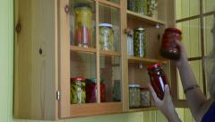Girl from kitchen dresser takes jars pickled peppers tomatoes Stock Footage