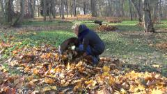 Gardener in the yard  poke autumn leaves in a fabric bag and go Stock Footage