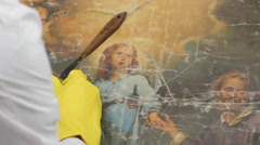 Restorer at work on damaged ancient painting Stock Footage