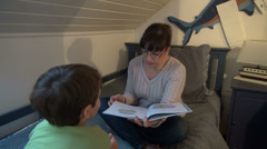 Loving mother reading from a book to her son, telling a story, room,quality time Stock Footage