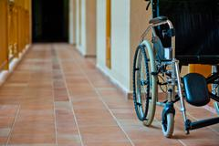 empty wheelchair in hospital corridor - stock photo