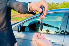 handing over keys of new car buyer - stock photo