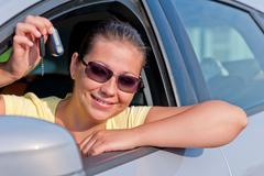 woman showing the key of her new car - stock photo