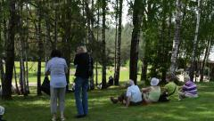 Tourists sit on grassand enjoy folk music and dances in festival Stock Footage